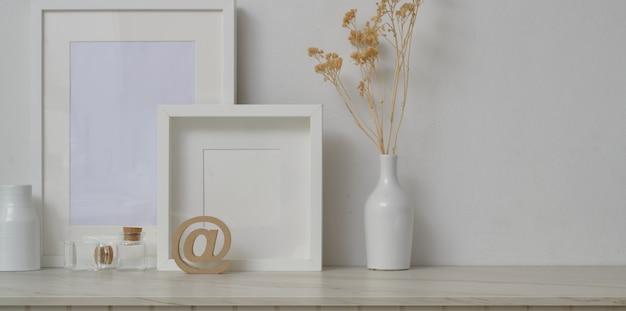Minimalna przestrzeń robocza z makietami ramek i dekoracjami w tle białej ściany