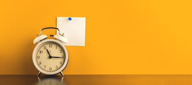Minimalne kreatywne zdjęcie koncepcyjne obszaru roboczego z przypiętym pustym papierem notatnika, baner z zegarem na stole, żółte zdjęcie w tle