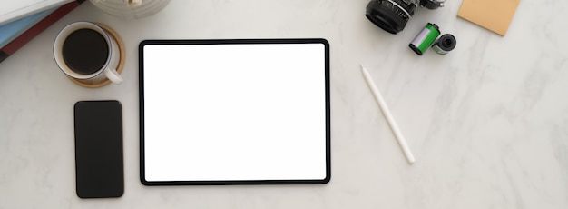 Minimalne miejsce pracy fotografa z makietą tabletu, smartfona, aparatu i innych materiałów eksploatacyjnych
