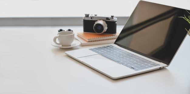 Minimalne miejsce pracy fotografa z otwartym laptopem, zabytkowym aparatem i filiżanką kawy