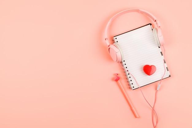 Minimalne miejsce pracy z pustym notatnikiem, słuchawki