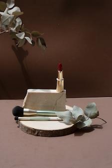 Minimalne nowoczesne produkty kosmetyczne wyświetlają pędzle do makijażu na tle naturalnych odcieni ziemi z nakładką cienia, kopią przestrzeni