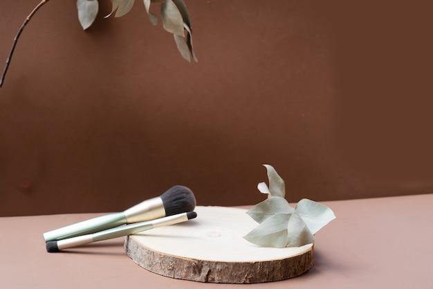 Minimalne nowoczesne produkty kosmetyczne wyświetlają pędzle do makijażu na tle naturalnych odcieni ziemi