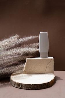 Minimalne nowoczesne produkty kosmetyczne wyświetlają się z tubą na tle naturalnych odcieni ziemi z nakładką cienia