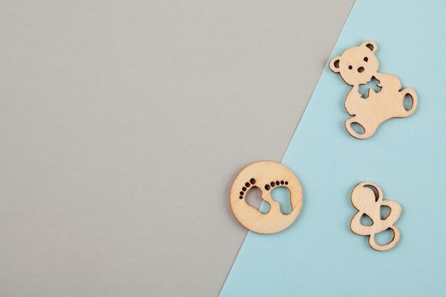Minimalne pastelowe tło dekoracyjne z małe drewniane figurki na urodziny noworodka