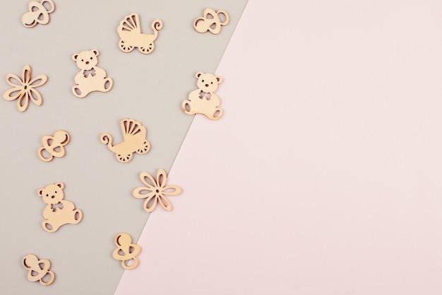Minimalne pastelowe tło dekoracyjne z małymi drewnianymi figurkami na urodziny noworodka
