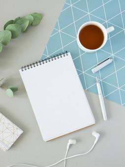 Minimalne poranne biurko. makieta notatnika z miejscem na tekst, słuchawki, herbatę i gałąź eukaliptusa. pionowy układ płaski