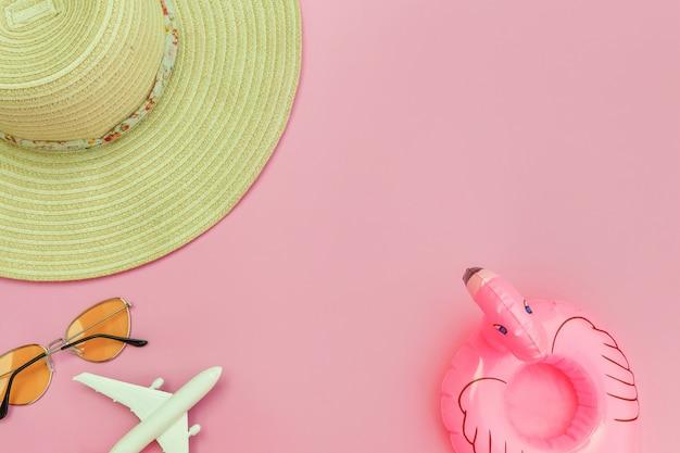 Minimalne proste mieszkanie leżało w płaskiej czapce z okularami przeciwsłonecznymi i nadmuchiwanym flamingiem na pastelowym różowym tle