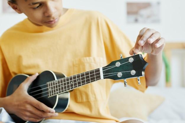 Minimalne przycięte zdjęcie nastoletniego chłopca grającego na ukulele siedząc na łóżku, kopia przestrzeń
