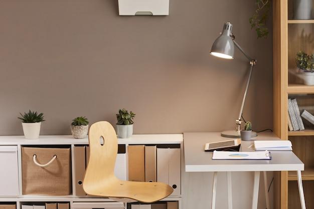 Minimalne tło przytulnego miejsca pracy oświetlonego ciepłym oświetleniem z metalowej lampy biurkowej, miejsce na kopię
