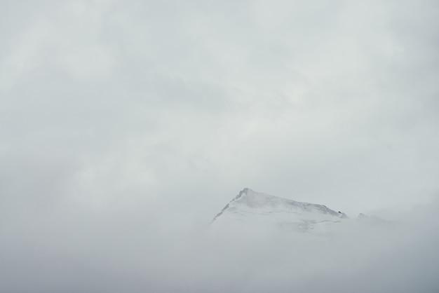 Minimalny górski krajobraz z wysoką spiczastą skałą w chmurach. minimalistyczna górska sceneria z ostrym ośnieżonym szczytem górskim nad chmurami. śnieżnobiały spiczasty szczyt nad białymi chmurami. duży top w gęstej mgle