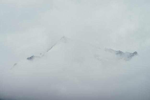 Minimalny górski krajobraz z wysoką spiczastą skałą w chmurach.