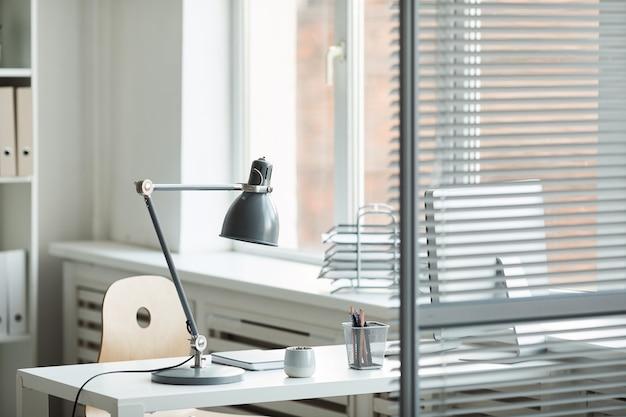 Minimalny obraz tła pustego miejsca pracy biurowej przez okno z białym biurkiem za szklaną ścianą, miejsce na kopię