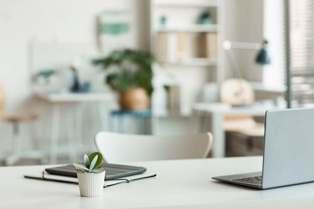 Minimalny obraz w tle zapraszania pustego miejsca pracy z białym biurkiem i sukulentów na pierwszym planie, miejsce na kopię