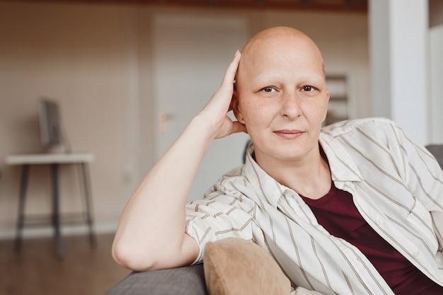 Minimalny portret łysej dorosłej kobiety patrząc na kamery siedząc na kanapie w ciepłym wnętrzu domu, łysieniu i świadomości raka, skopiuj przestrzeń