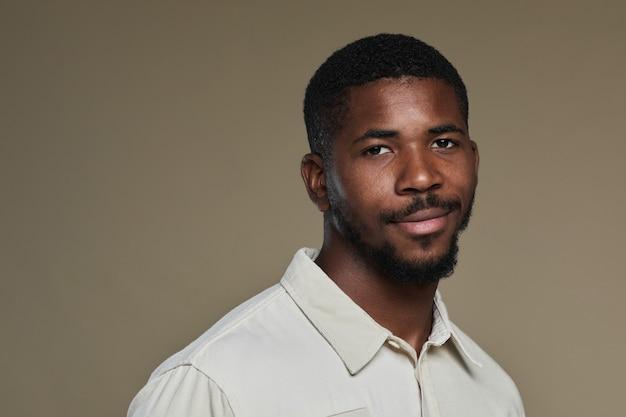 Minimalny portret młodego afroamerykanina patrzącego w kamerę i uśmiechającego się, pozując na przeciw...