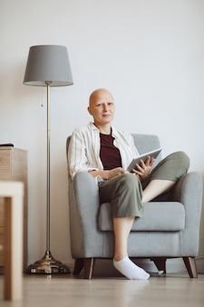 Minimalny portret pełnej długości łysej dorosłej kobiety trzymającej książkę i patrząc na kamerę w zamyśleniu, siedząc w wygodnym fotelu w domu, łysienie i świadomość raka