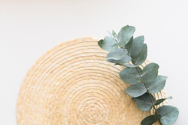 Minimalny pulpit z widokiem z góry. liście eukaliptusa na talerzu słomy. miejsce na napis.