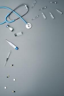 Minimalny skład sprzętu medycznego z antybiotykami i stetoskopem rozłożonym na szarym tle,