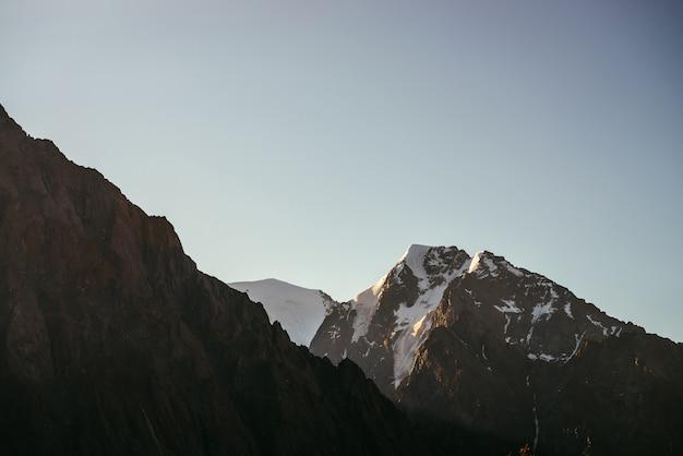 Minimalny słoneczny krajobraz z wysokim ośnieżonym szczytem w złotym słońcu. minimalistyczna sceneria wschodu słońca ze skałami i śniegiem w złotym świetle. malowniczy widok na wielki śnieżny szczyt o wschodzie słońca. słoneczny minimalizm