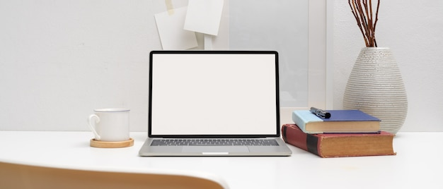 Minimalny stół roboczy z makietą laptopa, książek, filiżanki kawy i dekoracji