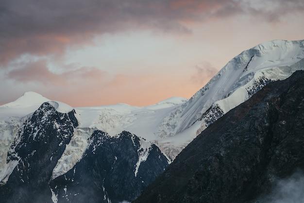 Minimalny świt alpejski krajobraz z ośnieżonym szczytem na tle zachodu lub wschodu słońca zachmurzonego nieba koloru pomarańczowego. nastrojowa sceneria gór ze śnieżnobiałym grzbietem górskim w pomarańczowym niebie świtu.