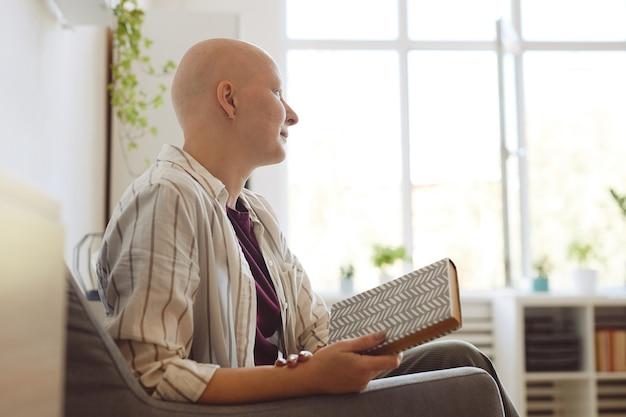 Minimalny widok z boku portret łysej młodej kobiety trzymającej książkę i odwracającej wzrok, siedząc w fotelu w domu, skopiuj miejsce