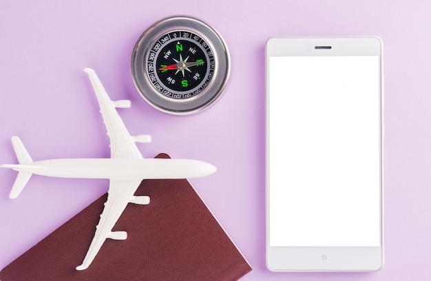 Minimalny zabawkowy model samolotu, kompas i pusty ekran nowoczesnego inteligentnego telefonu komórkowego