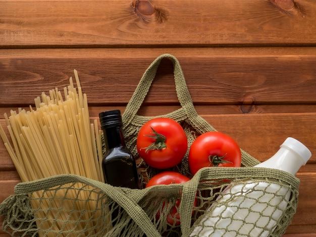 Minimalny zestaw produktów w bawełnianej torbie z siatki. makaron, olej, mleko, pomidor. wzrost cen produktów