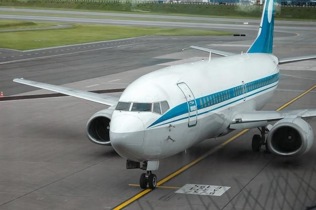 Mińsk, białoruś - 16 czerwca 2021 międzynarodowy port lotniczy mińsk. widok z okna znikał na pas startowy i samoloty. międzynarodowy transport pasażerski.