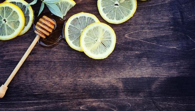 Miód i cytryna. kij miodu i plasterki cytryny w plasterkach na drewnianym stole. herbata w filiżance i słodki miód limonkowy w słoiku.