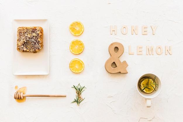 Miód i herbata cytrynowa z plastrem miodu, plasterkami cytryny i rozmarynem
