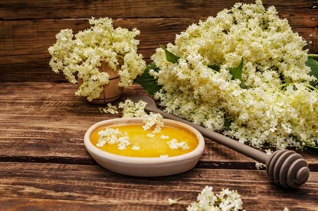 Miód i świeże kwiaty bzu czarnego. pachnący bukiet, medycyna alternatywna