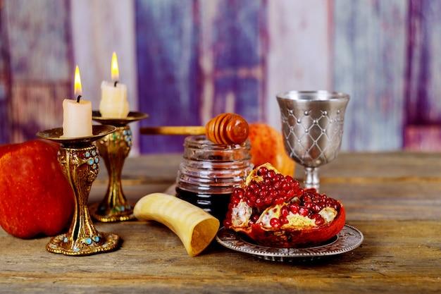 Miód, jabłko i granat na drewnianym stole na tle bokeh