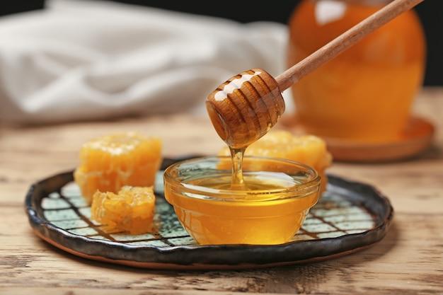 Miód kapie z drewnianej łyżki do szklanej miski na stole, zbliżenie