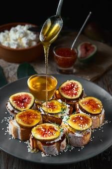 Miód kapie z łyżki na kanapki figowe na bagietce z tostowego sera koziego na talerzu
