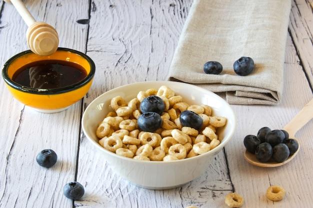 Miód krąży płatki zbożowe z mlekiem i jagodami w misce na drewnianym stole na tle zdrowe śniadanie