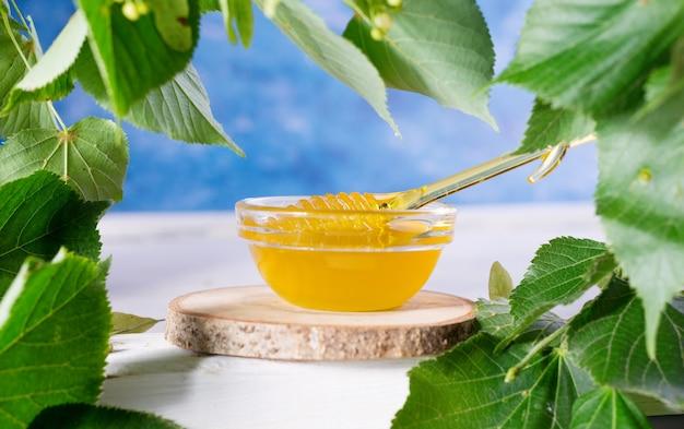 Miód lipowy w słoiku i miska z czerpakiem miodu na białym drewnianym stole