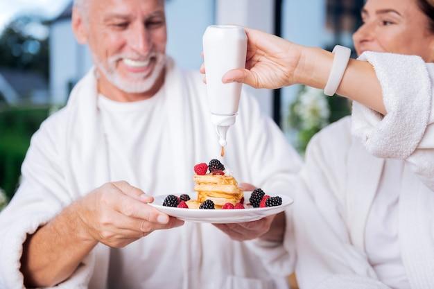Miód na naleśniki. piękna żona ubrana w biały inteligentny zegarek na rękę, która używa miodu do naleśników podczas śniadania z mężem