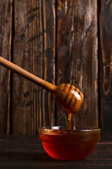 Miód płynie z patyka do słoika. nieociosana słodka fotografia, drewniany tło, copyspace.