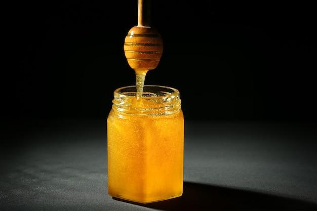 Miód przelewa się z chochla do szklanego słoika w ciemnym miejscu