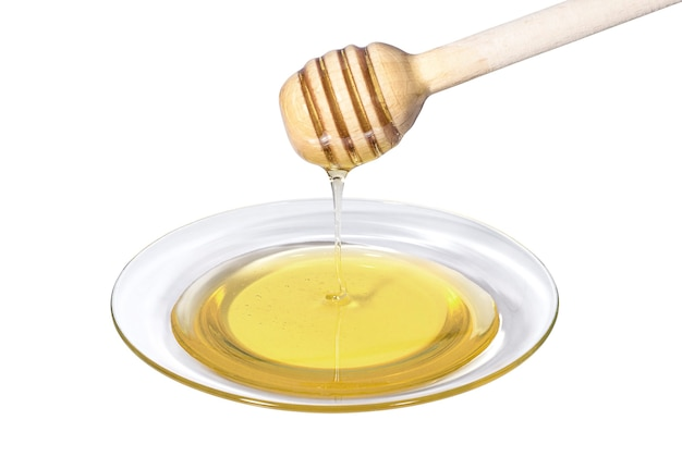 Miód pszczeli kapie z drewnianego kubka na przezroczysty szklany talerz
