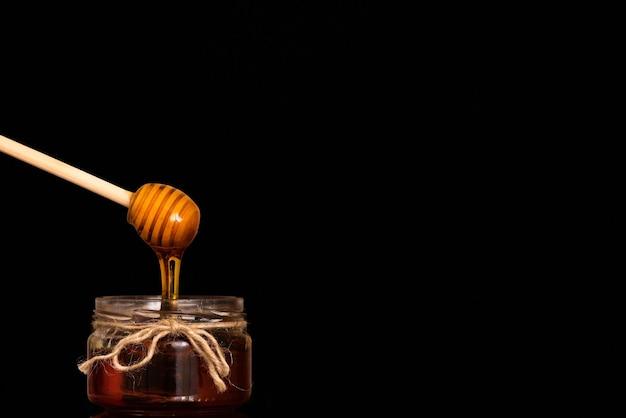 Miód spływa z łyżki do szklanego słoika.