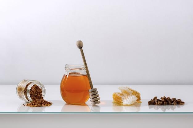 Miód tło. produkty pszczelarskie miód, pyłek, propolis, plaster miodu na drewnianym stole. skopiuj miejsce swojego tekstu.