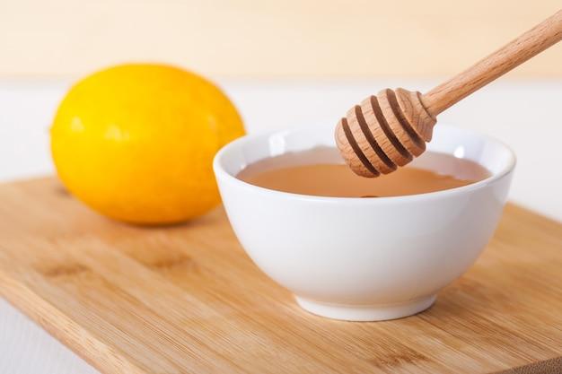 Miód w białej ceramicznej misce z miodem i cytryną na drewnianej desce kuchennej.