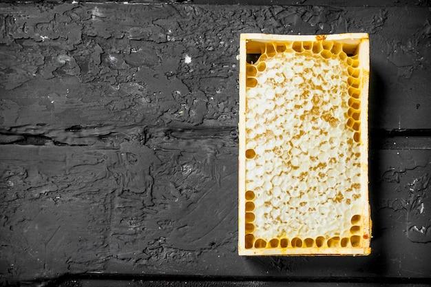 Miód w drewnianych plastrach miodu. na czarnym rustykalnym.