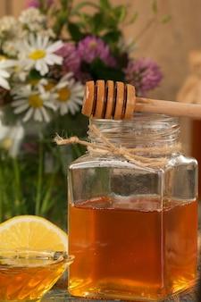Miód w garnku lub słoiku na drewnianym stole