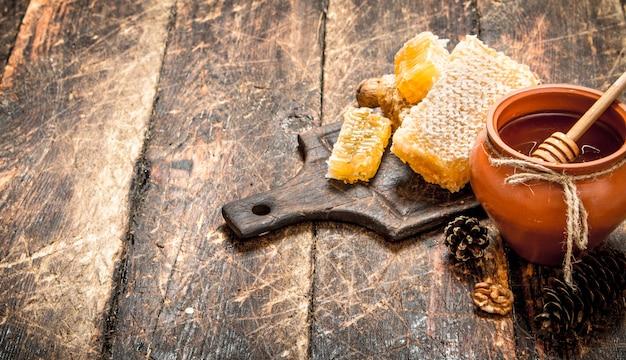 Miód w garnku z orzechami i szyszkami na drewnianym stole.