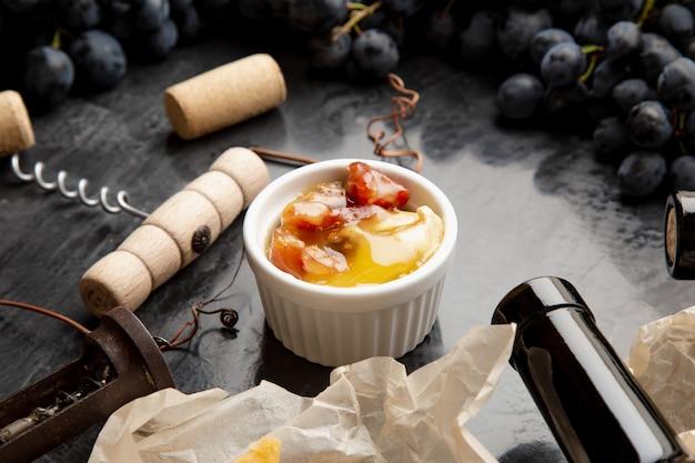 Miód w słoiku na ciemnym kamiennym stole z korkociągiem z serem winnym w ramce z soczystych winogron black. pyszny żółty miód pszczeli zmieszany z orzechami i suszonymi owocami w talerzu z przekąskami na czarnym stole.