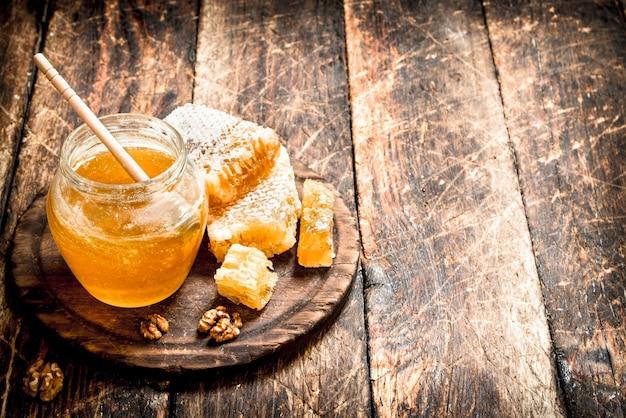 Miód w słoiku z orzechami. na drewnianym tle.